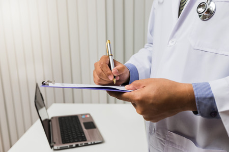 Doctor in gown uniform using a pen write on medical chart. Medicine and health care concept. Standard-Bild - 116540154