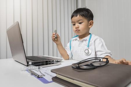 little boy in medic uniform holding a pen on desk. Standard-Bild - 116540152