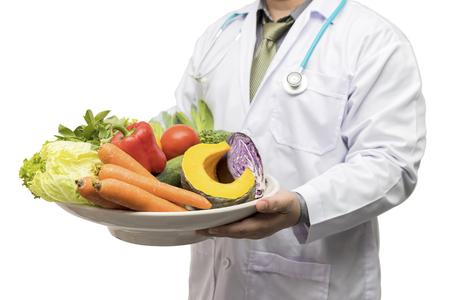 Doctor holding basket assort fresh fruits and vegetables isolated on white background. Standard-Bild - 116540160