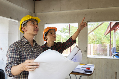 Engineer and architect discussing with foreman about project in building construction site Standard-Bild - 116540156