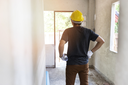 Engineer or Architect holding blueprint in building construction site. Standard-Bild - 116540161