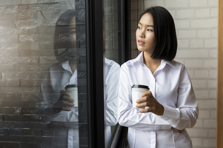 Happiness businesswoman holding takeaway coffee cup while standing at the window in the office. Standard-Bild - 116540552