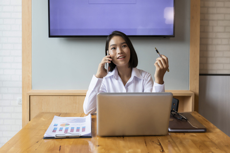 Businesswoman talking on the phone and smiling. Secretary answering her cellphone. Standard-Bild - 116540555