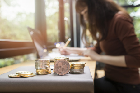 Copper Ripple coin (cryptocurrency) in front of businesswoman background. New Virtual money concept Standard-Bild - 116540557