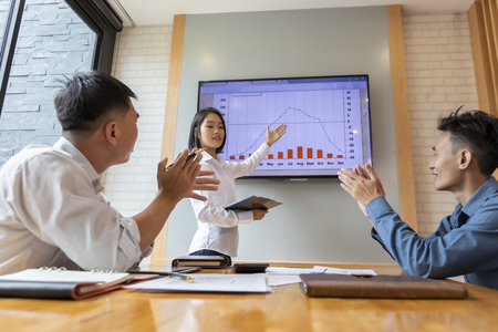 Beautiful businesswoman gives report or presentation to her business colleagues in the conference room. She show graphic charts and company's growth on the wall TV. Standard-Bild - 116540560