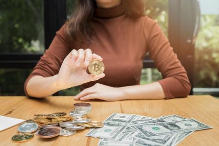 Golden bitcoin (cryptocurrency) in hand of businesswoman. New Virtual money concept Standard-Bild - 116540558