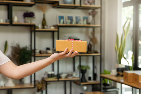Closeup hands of delivery man holding parcel package to deliver. Standard-Bild - 116540559