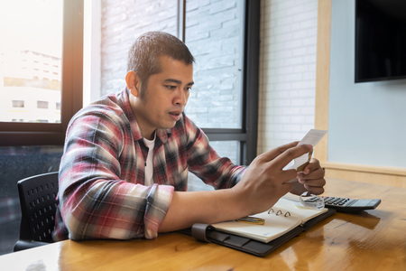 Asian man calculating expences, trying to solve budget problems, looking at papers, managing with utility bills. Standard-Bild - 116540563
