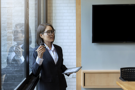 Asian businesswoman using a digital tablet while leaning against the window in an office. Standard-Bild - 116540570