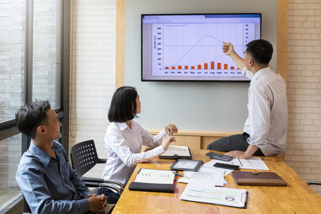 Businessman gives report or presentation to his business colleagues in the conference room. He show graphic charts and company's growth on the wall TV. Standard-Bild - 116540571