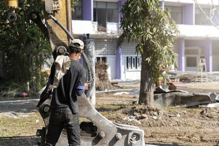 The mechanic is repairing the arm of the drilling excavator. Standard-Bild - 116540692