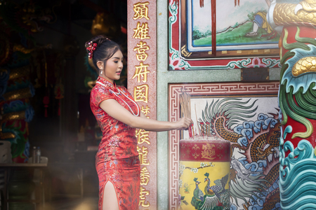 Concept to celebrate Chinese New Year : Chinese woman in a red cheongsam dress holding incense pay homage to Chinese god at shrine. Standard-Bild - 116540699