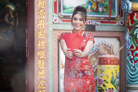 Concept to celebrate Chinese New Year : Chinese woman in a red cheongsam (qipao) dress holding red envelopes (hong bao) at shrine. Standard-Bild - 116540705