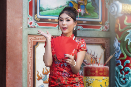 Concept to celebrate Chinese New Year : Chinese woman in a red cheongsam (qipao) dress holding red envelopes (hong bao) at shrine. Standard-Bild - 116524652