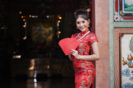 Concept to celebrate Chinese New Year : Chinese woman in a red cheongsam (qipao) dress holding red envelopes (hong bao) at shrine. Standard-Bild - 116524655
