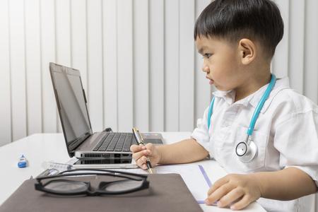 little boy in medic uniform holding a pen on desk. Standard-Bild - 116524654