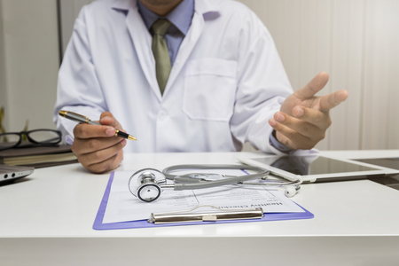 Medicine and health care concept. Close-up of stethoscope is lying on the clipboard near a doctor consults patient. Standard-Bild - 116524659