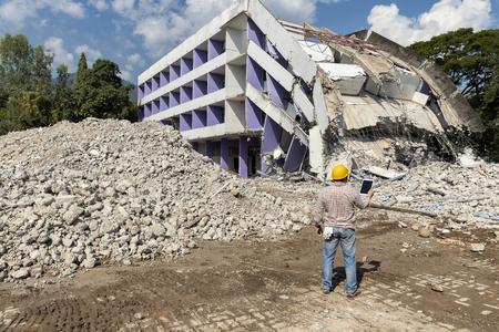 Engineer holding tablet is checking for destruction, demolishing building. Standard-Bild - 116540834
