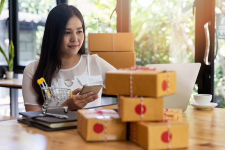 Woman are receiving orders via cell phone. Successful entrepreneur business woman with online sales and Parcel shipping in her home office. Standard-Bild - 116524700