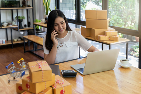 Woman are receiving orders via cell phone. Successful entrepreneur business woman with online sales and Parcel shipping in her home office. Standard-Bild - 116524701