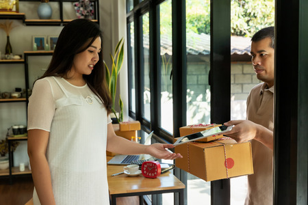 Woman received the parcel delivery to the house. Woman signing to get her package. Standard-Bild - 116524704