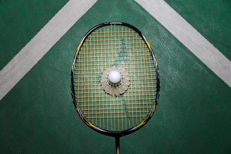 Top view of white badminton shuttlecock and racquet on wooden floor. Standard-Bild - 121847960