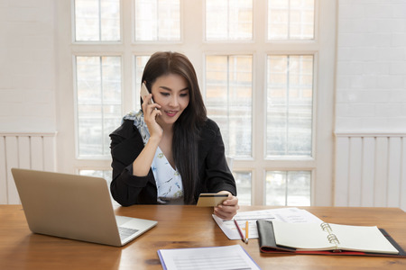 Young asian woman holding credit card and using smart phone for purchase product on internet in home office. Online shopping concept.