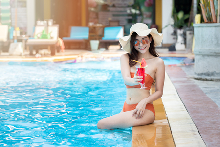 Sexy young asian woman in swimsuits in summer. beautiful woman in orange bikini with sunglasses and tropical drink sitting in swimming pool. Standard-Bild - 121848153