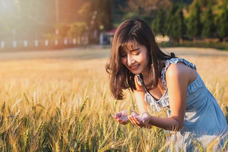 Beautiful and happy asian woman enjoying life in barley field at sunset. Standard-Bild - 121848154
