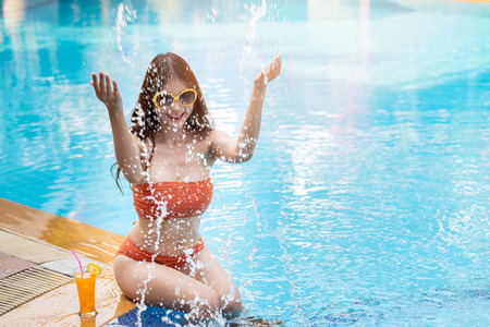 Summer vacation and holiday tropical concept. Sexy and beautiful asian woman in orange bikini splashing water on border of  swimming pool. Standard-Bild - 121848150