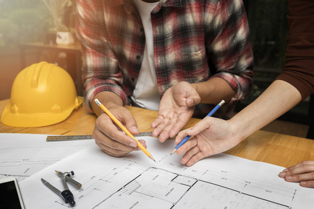 Group of two coworkers working with blueprint in office. co-working teamwork concept. Standard-Bild - 121848159