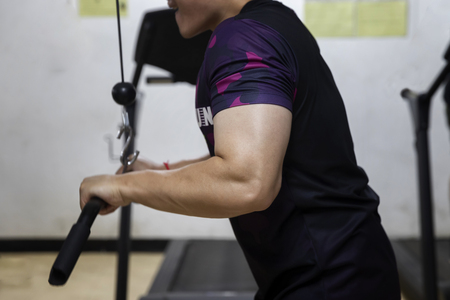 A man workout with Cable Triceps Pushdown in gym. Standard-Bild - 121848158