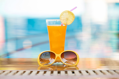Summer holiday tropical concept. Fresh  orange juice and sunglasses on border of a swimming pool. Standard-Bild - 121848163