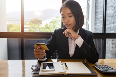 Young asian woman holding credit card purchase product on internet in home office. Online shopping concept. Standard-Bild - 121848304