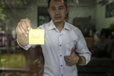 Motivation Concept. Businessman holding sticky note with