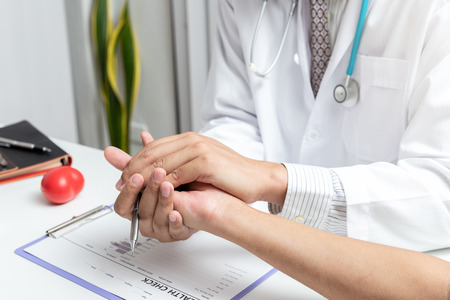 Doctor holding patient's hand for encouragement, empathy, cheering and support while medical examination. Bad news lessening, medicine and health care concept . Standard-Bild - 121848314
