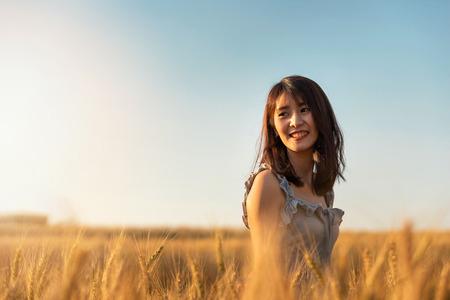 Beautiful and happy asian woman enjoying life in barley field at sunset. Standard-Bild - 123831246