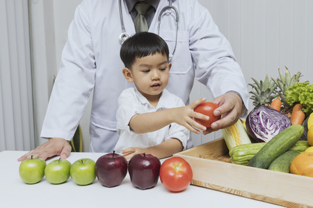 A boy and doctor happy to have healthy food. Kid learning about nutrition with doctor to choose eating fresh fruits and vegetables. Standard-Bild - 123831248