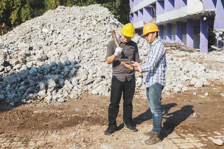 Demolition control supervisor and contractor discussing on demolish building. Standard-Bild - 123831263