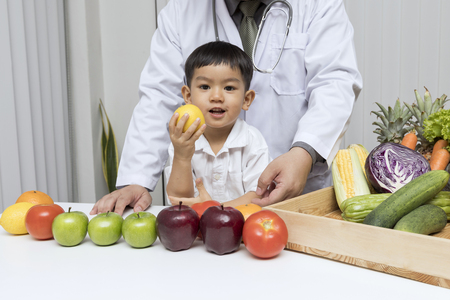 A boy and doctor happy to have healthy food. Kid learning about nutrition with doctor to choose eating fresh fruits and vegetables. Standard-Bild - 123831270