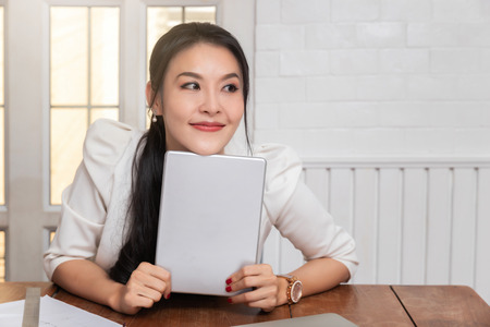 Business successful concept. Asian businesswoman holding tablet and she smiled in a good mood. Standard-Bild - 123831325