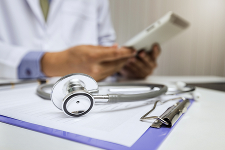 Close-up of stethoscope is lying on the clipboard in front of a doctor.