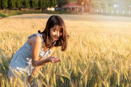 Beautiful and happy asian woman enjoying life in barley field at sunset. Standard-Bild - 123831328