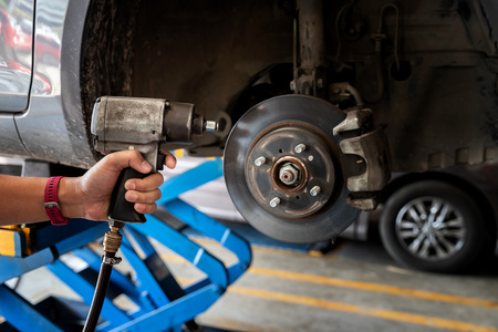 Car service, repair and maintenance concept - auto mechanic man with electric screwdriver changing tire in auto repair shop. Stock Photo