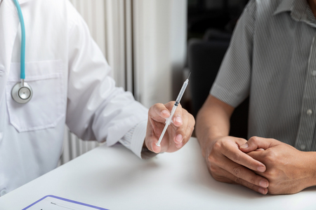 Medical, medicine, vaccination and health care concept. Doctor with syringe doing injection of vaccine to male patient while sitting at the table in office.