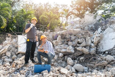 Demolition control supervisor and contractor using tablet to planning on demolish building.