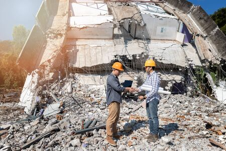 Engineers shaking hands in demolish building. Agreement between structural engineers and contractors after agreeing the cost of construction and repair real estate.
