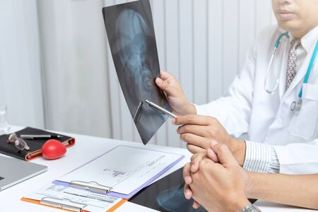 Medical and health care concept. Doctor explaining x-ray results to patient while sitting at the table in office. Stock Photo