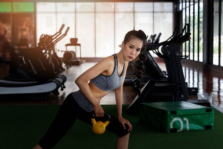 Fitness woman doing workout triceps with kettlebell at gym. Healthy lifestyle concept.