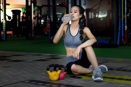 Fitness woman drinking water while sitting and resting on the floor in gym. Healthy lifestyle concept.